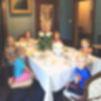 Six children sitting around a rectangular dining table decorated with Victorian table settings