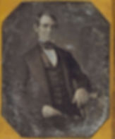 Historic image of Abraham Lincoln as a young man in a suit and cravat. Image is scratched across its entirety and set into an octogonal frame.