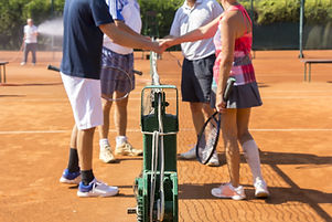 Mixed doubles tennis players shake hands