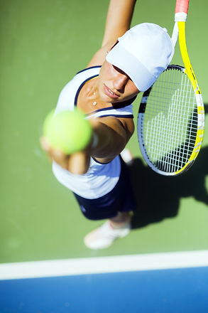 Beautiful female tennis player serving o