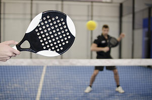 Paddle tennis copuple playing in court w