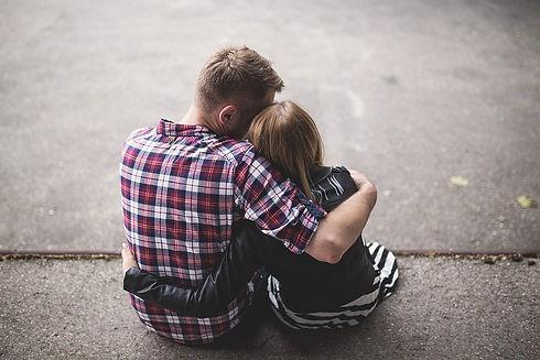 Ein Ehepaar das sich in Arm hält und auf dem Boden sitzt