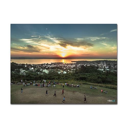Fotografia aérea tirada com drone do pôr do sol do Parque Natural Morro do Osso com gente tomando chimarrão e jogando futebol