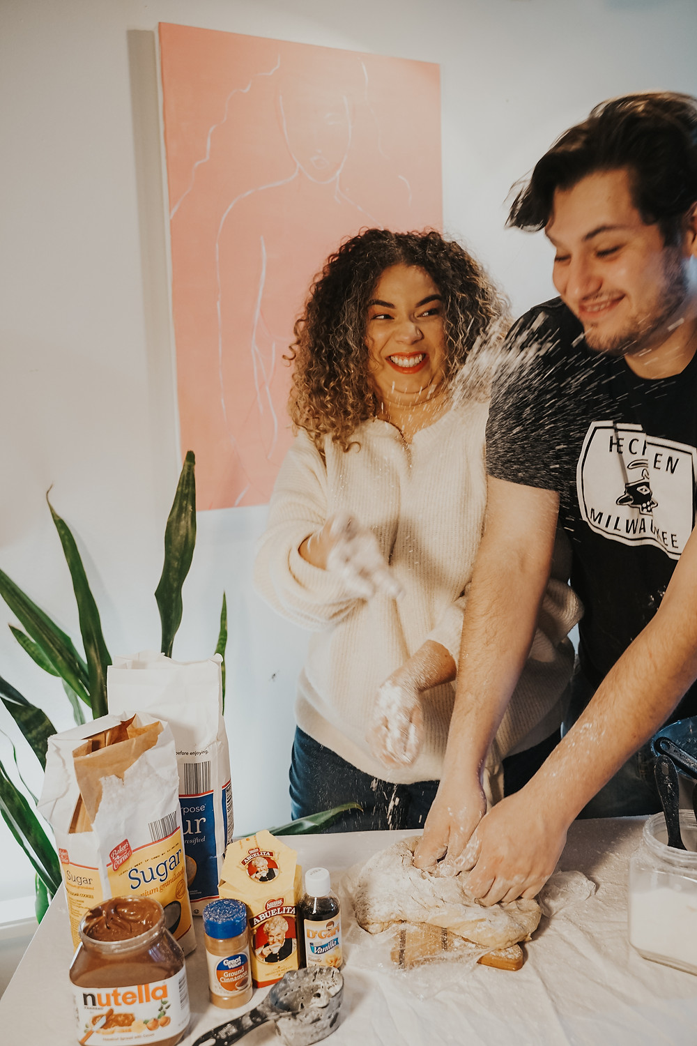 wife throwing baking powder at husband during at home engagement session