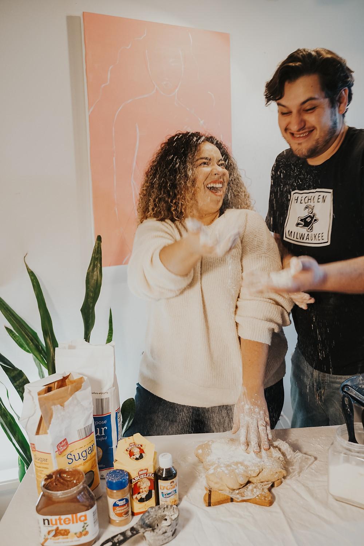 husband wearing hecho en milwaukee shirt while baking with wife