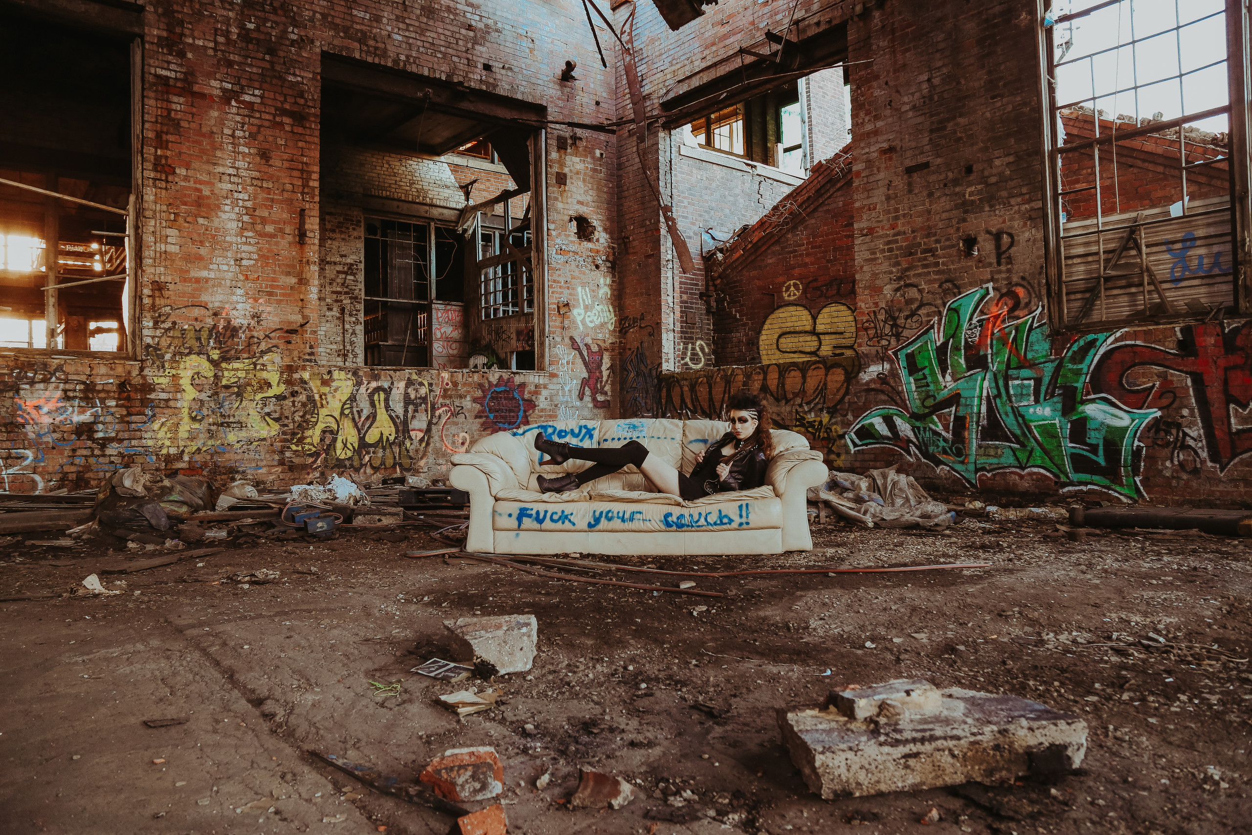 model laying on dirty fuck your couch in abandoned warehouse in milwaukee, wisconsin