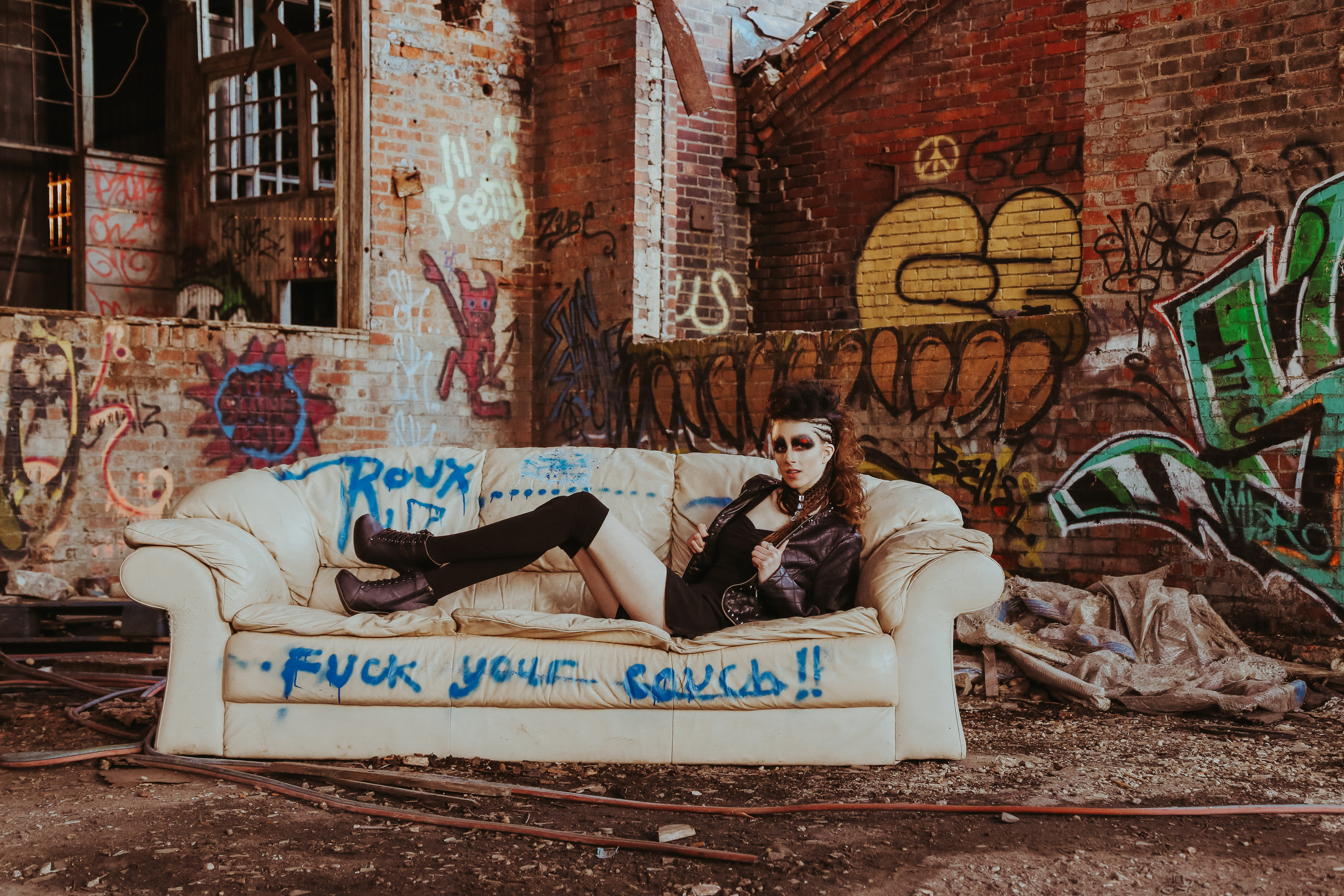 model in abandoned warehouse with graffiti and dirty couch
