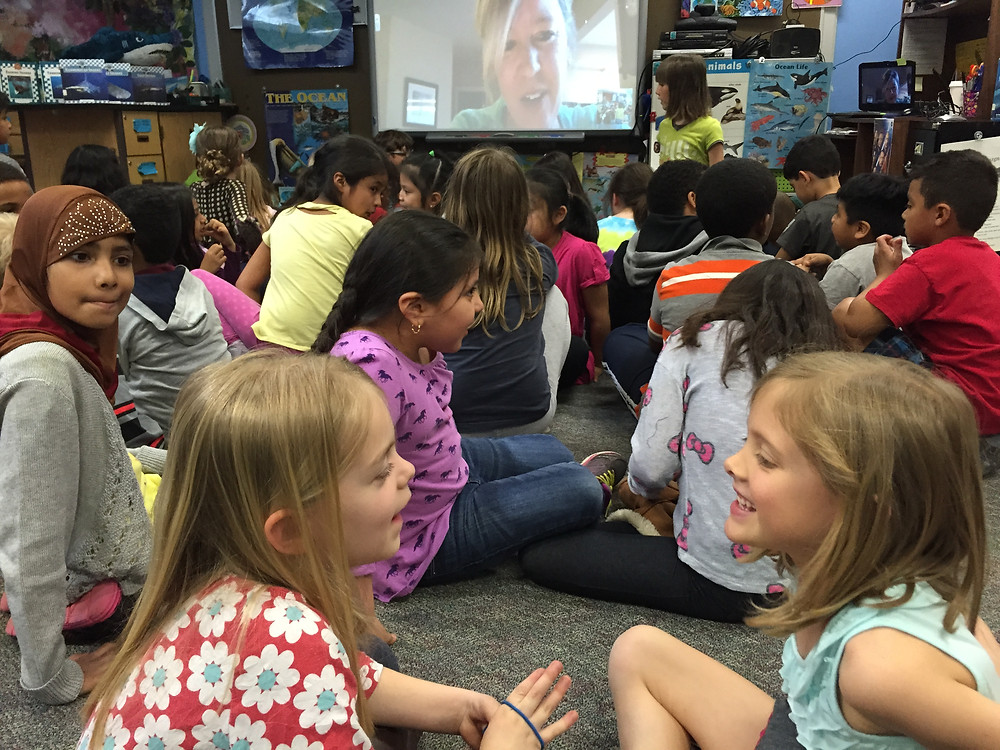 A group of elementary students turn and discuss a topic while sitting in front of a visitor who is video-calling their classroom.