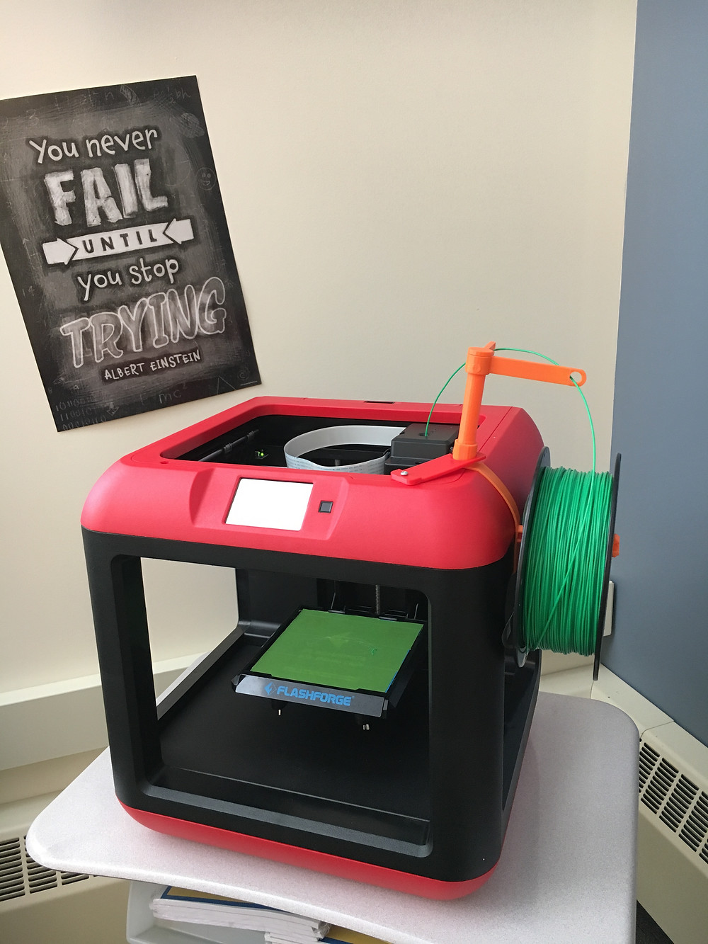 "This picture contains a Flashforge Finder 3d printer loaded with green PLA filament. In the background, a poster reads ""You never fail until you stop trying. Albert Einstein"""
