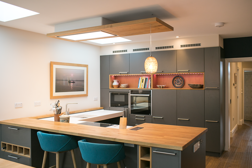 Wheelchair accessible kitchen with large peninsula with solid wood worktop to foreground, and tall units with integrated ovens to rear wall. Large l-shaped rise and fall worktop in sold surface material with sink and hob to left of image.