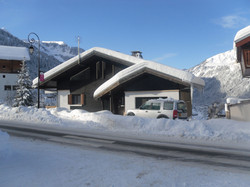 chalet from road with bus stop