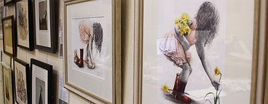 In-store art gallery featuring a range of framed artwork, including Sue Warner's paintings