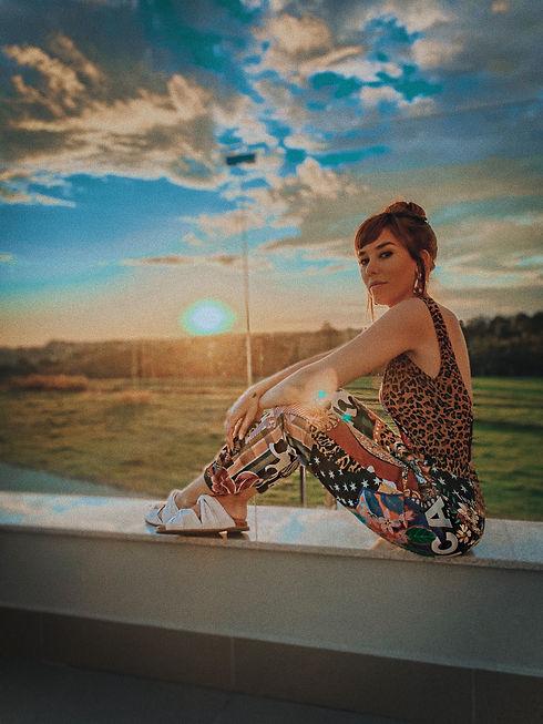Dj Aline Rocha sentada na varanda com um