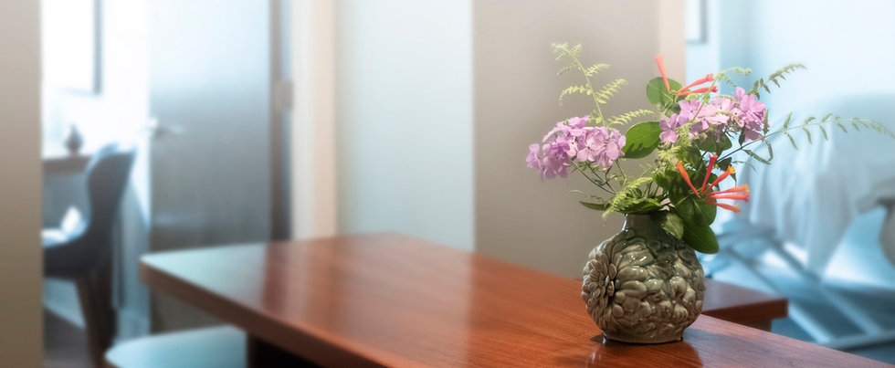 A bouguet of native flowers on the front desk with light filled treatment rooms behind