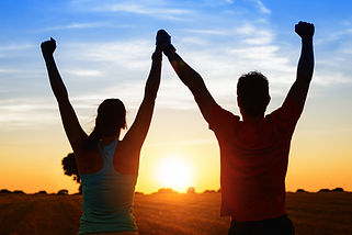 Successful couple of young athletes raising arms to golden summer sunset sky after trainin