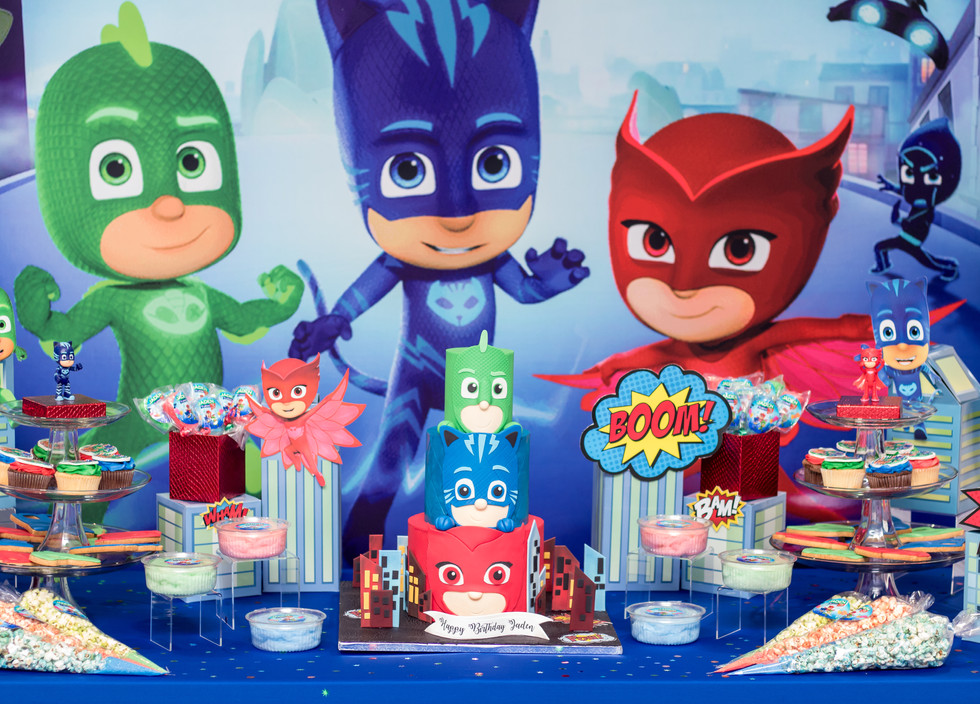 PJ Masks Dessert Bar featuring our show piece three-tier cake and sugar cookies. Kindly note that popcorn, candy and cupcakes displayed were not designed by With Love By Esther James