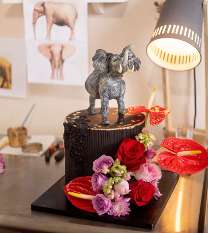 Black birthday cake featuring bas relief, handmade chocolate elephant and fresh florals