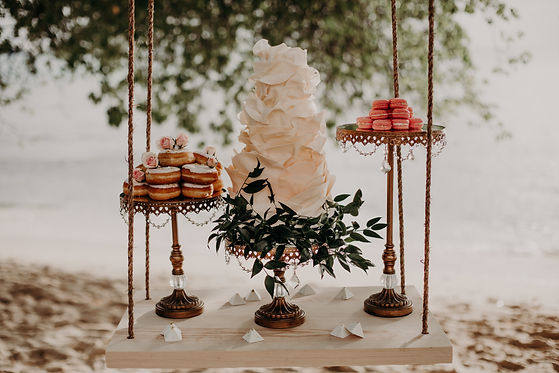 wedding cake with ruffles, donuts and macarons on the beach