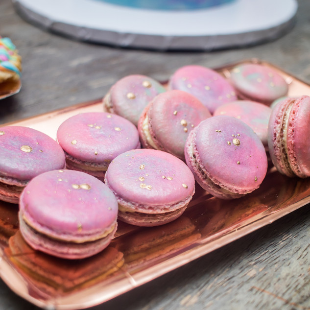 Platter of unicorn, watercolor macarons adorned with 24K gold