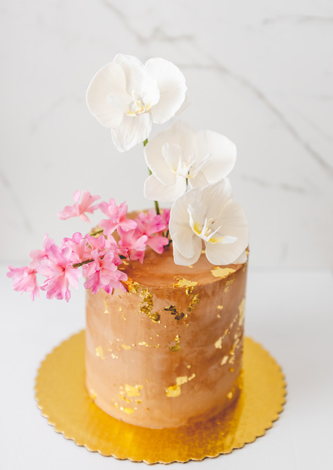 Chocolate buttercream cake featuring gold leaf and sugar flowers