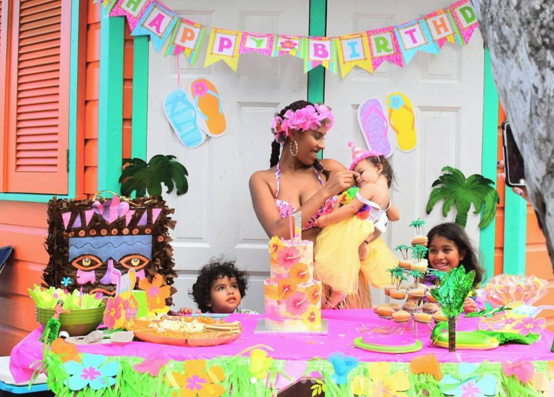 Beach Themed 1st Birthday Party featuring our two tier buttercream cake featuring fondant designed hibiscus flowers. Kindly note that other treats displayed were not designed by With Love By Esther James.