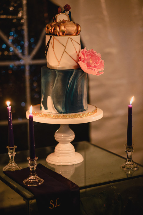 Two tier whimsical wedding cake- features gold geometric design, navy marbling, edible gold convertible with wedding couple and gum paste peony