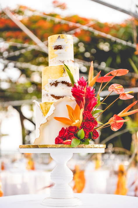 Three Tier Naked Wedding Cake featuring Fresh Tropical Florals and Gold Leaf Gilding. This Cake is Finished with a Fondant Wrapped Base Tier.