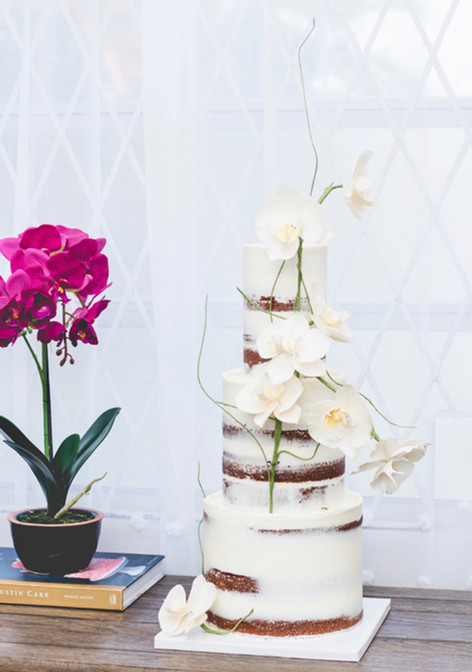 Three tier semi-naked wedding cake featuring sugar orchids