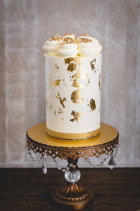 One Tier Buttercream Cake Gilded in Gold Leaf and Topped with Buttercream Swirls and Sprinkles