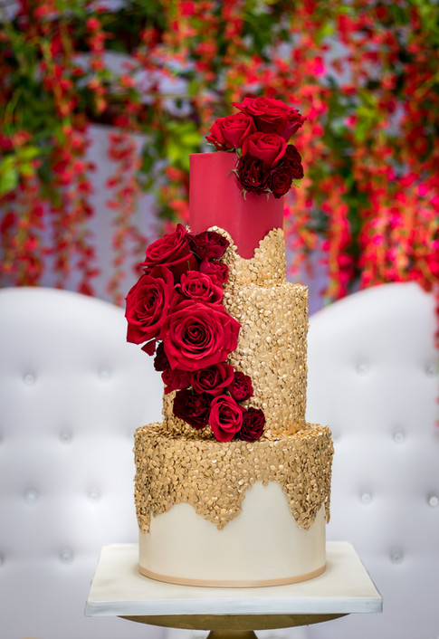 Red and gold three tier wedding cake featuring dripping gold sequins and fresh red roses