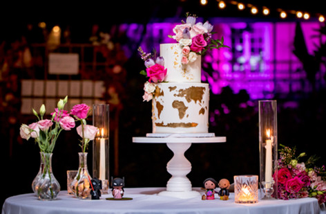 Two Tier Travel Themed Wedding Cake featuring florals and gold world map