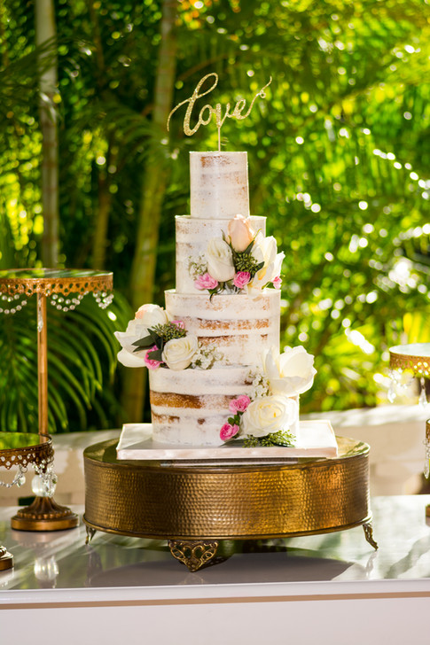 Four Tier Semi-Naked Wedding Cake adorned with fresh flowers