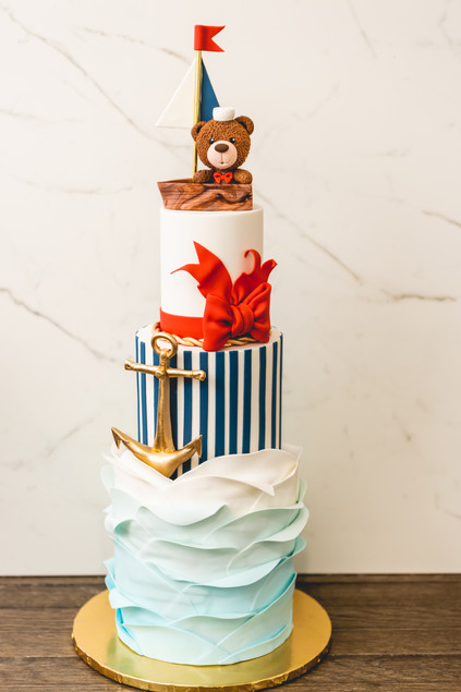 Three Tier Nautical Themed Birthday Cake featuring Sugar Waves, Gold Edible Anchor and Edible Teddy Bear in Sail Boat