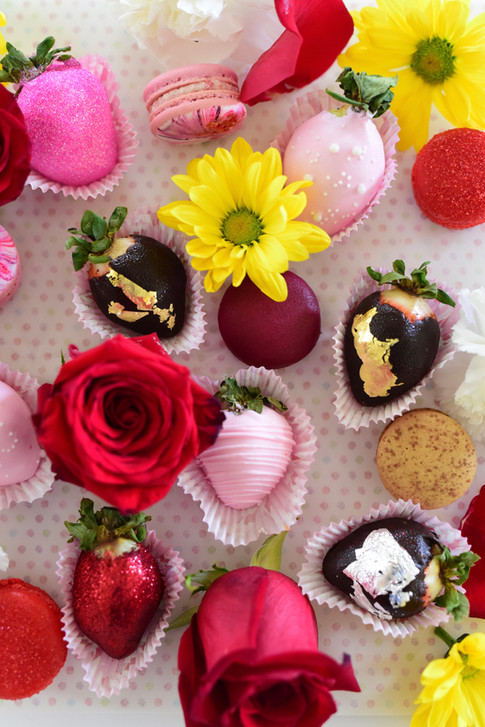 Aerial view of chocolate covered berries, macarons and fresh flowers