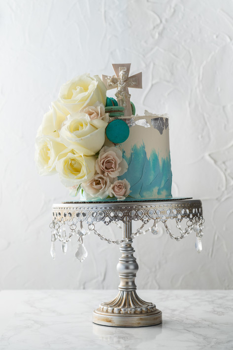 One Tier Watercolor Christening Cake featuring a cascade of fresh flowers and macarons. Finished with white, gumpaste cross topper