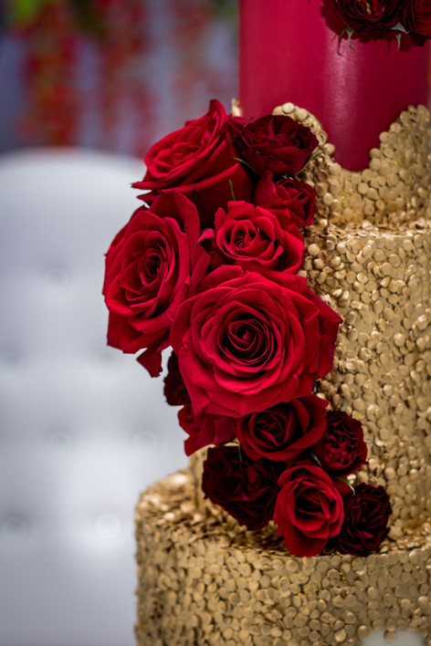 Closeup of Wedding Cake featuring Red Roses and Gold Sequins