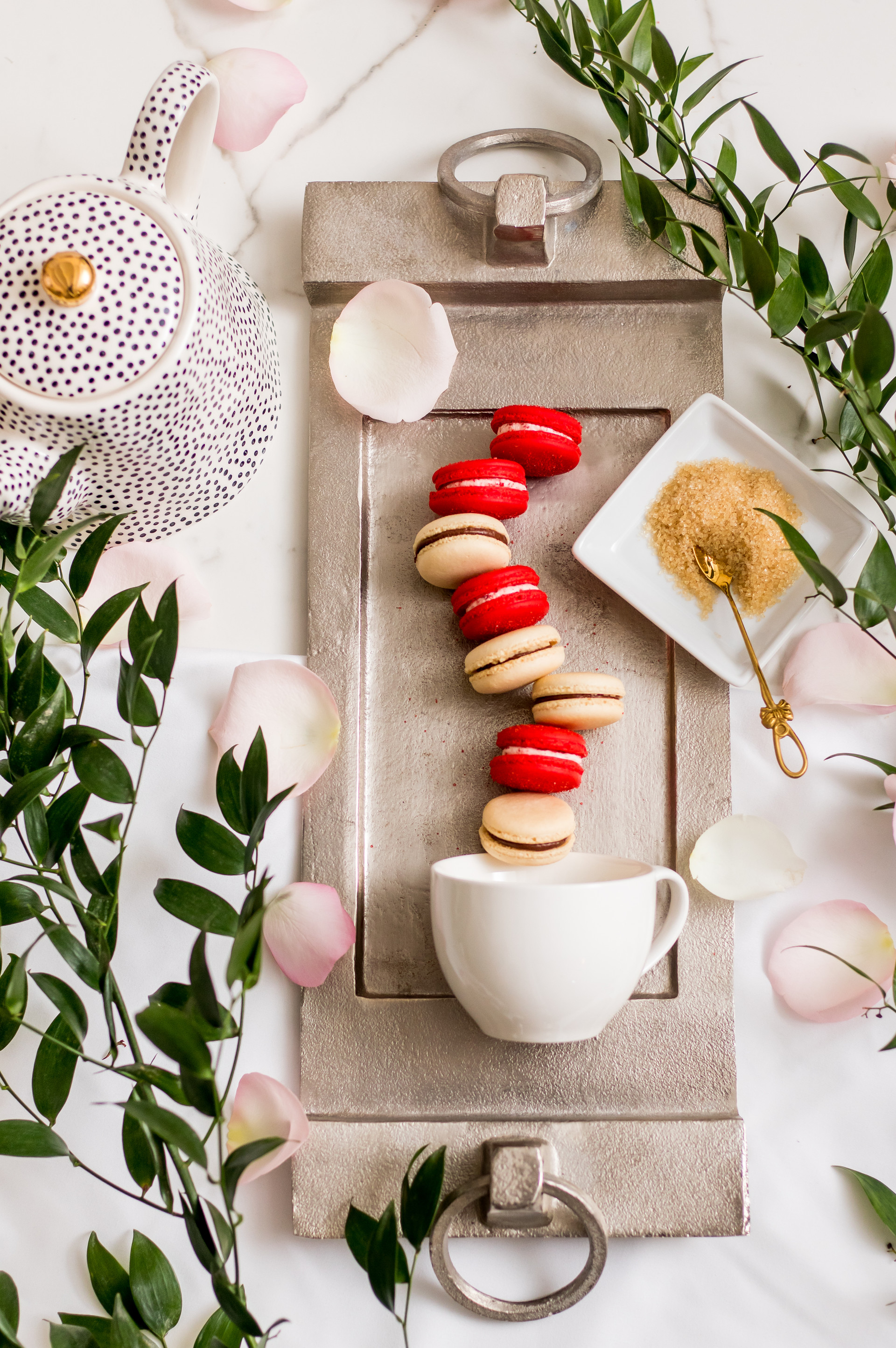 Macarons on silver tray with teapot and