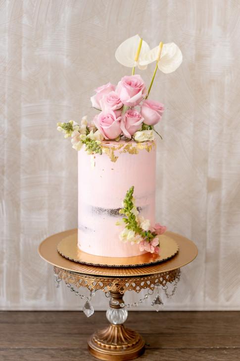 Blush pink buttercream birthday cake with fresh flowers