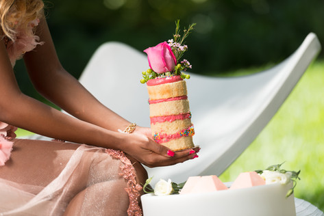Model sits with naked buttercream cake finished with fresh flowers