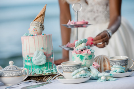 Beach themed wedding dessert table featuring drip cake, clam shell meringues and macarons