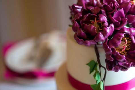Closeup of Wedding Cake featuring Sangria colored Gumpaste Peonies