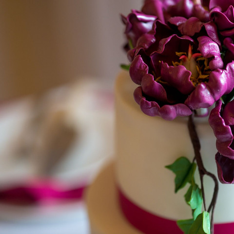 wedding cake with plum colored gum paste peonies