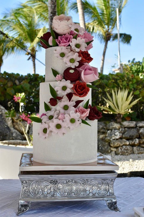All white three tier wedding cake- designed with lace stencilling and cascading gumpaste flowers