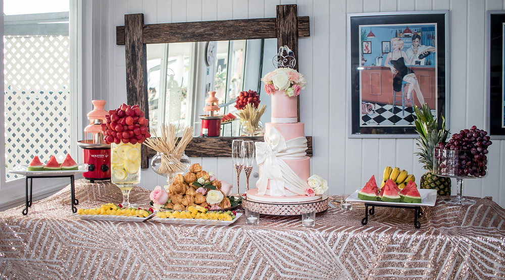 Peach colored wedding cake with over-sized pearl bow. Table features chocolate fountain display with fresh fruit.