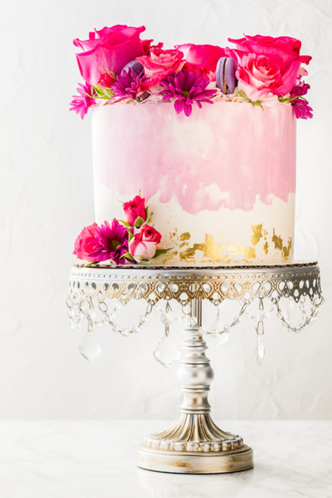 """One tier 8"""" Birthday Cake with halo of florals and macarons. Finished with 24K gold leaf"""