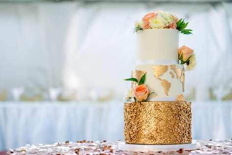 Three tier Gold & White Wedding Cake featuring World Map, Fresh Flowers and Gold Sequins