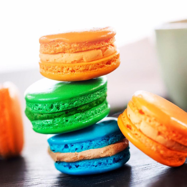 Stack of bright colored macarons- Flavors: orange (mango), green (pistachio), blue (hazelnut)