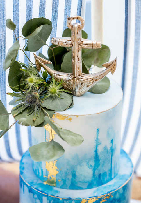 Blue and gold nautical themed wedding cake featuring edible anchor