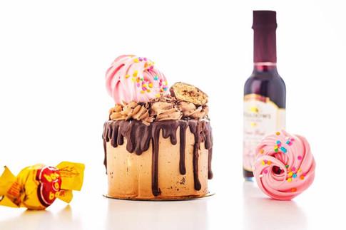Mini Buttercream Chocolate Drip Cake topped with meringue kisses