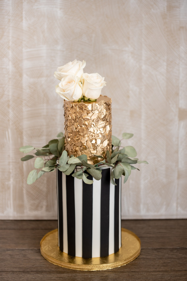 Two tier gold, black and white birthday cake featuring roses and eucalyptus